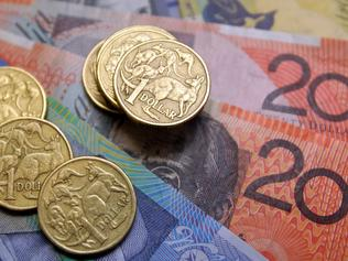 Australian one-dollar coins sit with a collection of banknotes arranged for a photograph, in Sydney, Australia, on Wednesday, Aug. 3, 2011. Australia's central bank may need to resume increasing the developed world's highest borrowing costs to keep inflation from accelerating as a mining boom intensifies, according to the International Monetary Fund. Photographer: Sergio Dionisio/Bloomberg