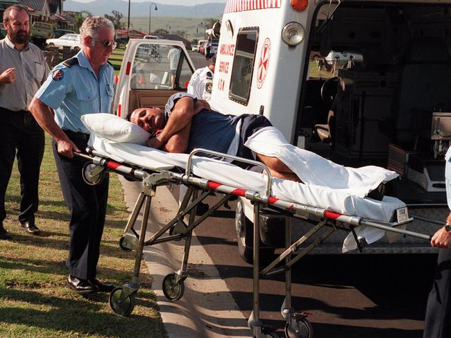 Matthew De Gruchy is taken away by ambulance officers after 'discovering' the bodies.
