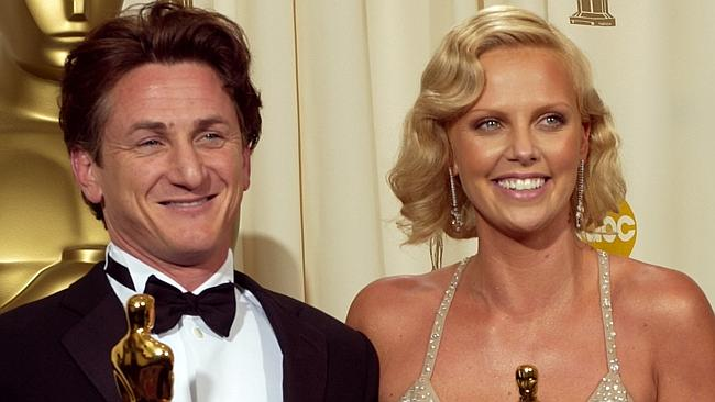 Charlize Theron with Sean Penn holding Oscar statues after winning Best Actress and Actor awards at 76th Academy Awards in 20...