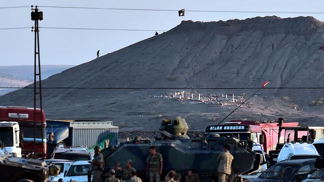 Seized ... Islamic State militants stand next to their flag atop a hill in the Syrian town of Kobane.