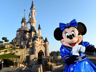 Disney character Mini mouse poses in front of the Sleeping Beauty Castle to mark the 25th anniversary of Disneyland - originally Euro Disney Resort - on March 16, 2017 in Marne-La-Vallee, east of the French capital Paris. The 25th anniversary celebrations will begin on March 26, 2017 with parades, various shows and a firework's display. / AFP PHOTO / BERTRAND GUAY