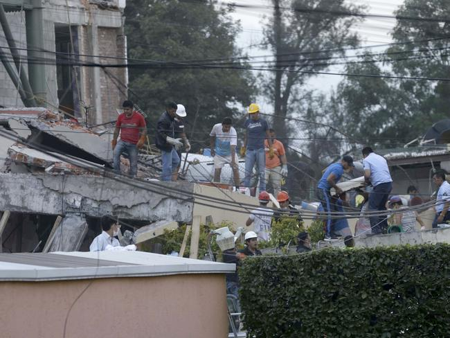 Volunteers and rescue personnel work on the remains of a collapsed primary school in an attempt to find children they believe are trapped under the rubble. Picture: AP / Marco Ugarte