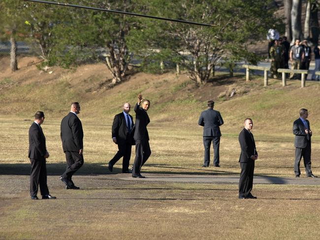 Into Brisbane ... President Barack Obama, centre, surrounded by members of the Secret Service, waves after stepping off the Marine One helicopter upon his arrival at Victoria Park. Picture: AP Photo/Pablo Martinez Monsivais