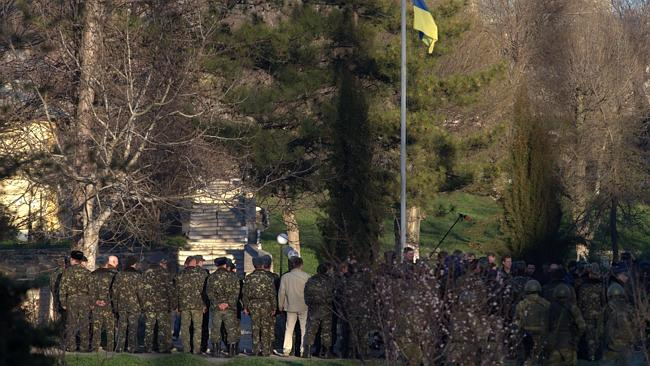 Standing firm... Ukrainian soldiers stand by the Ukrainian flag at the Belbek base. Picture: Ivan Sekretarev/AP