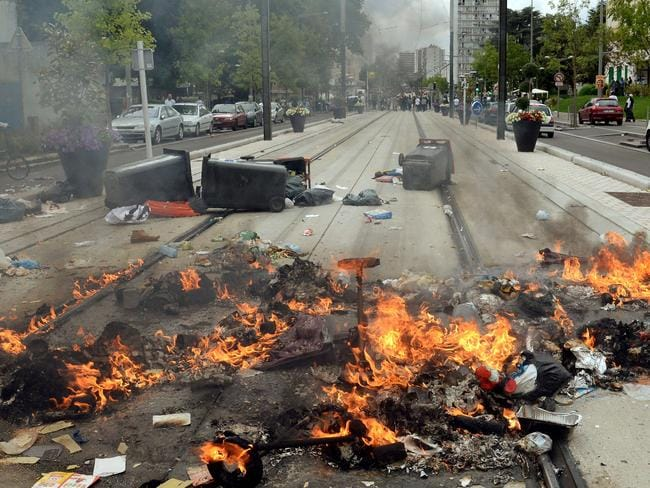 Burning detritus seen along the tramway line in Sarcelles. AFP PHOTO / PIERRE ANDRIEU