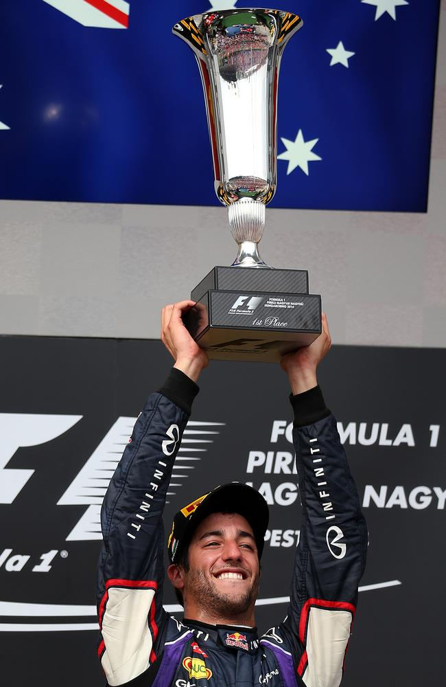 Ricciardo hoists the trophy under the Australian flag.