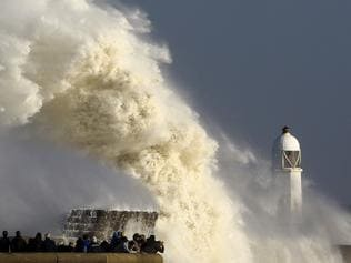 """TOPSHOT - Huge waves strike the harbour wall and lighthouse at Porthcawl, south Wales, on October 16, 2017 as Storm Ophelia hits the UK and Ireland. Ireland was hit by an """"unprecedented storm"""" on Monday that left two people dead, 120,000 homes and businesses without power and closed every school in the country. The storm also sent strong winds over the southwest of England and the south and west of Wales. / AFP PHOTO / Geoff CADDICK"""