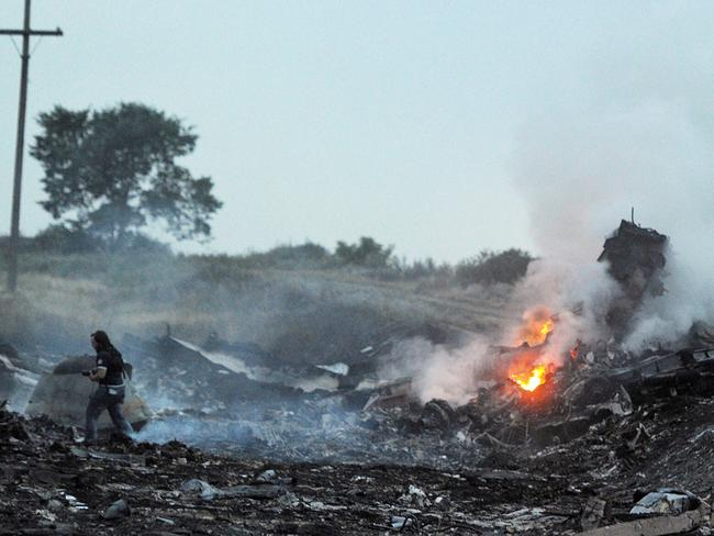 People stand among the wreckages of the Malaysia Airlines plane carrying nearly 300 passengers after it crashed in rebel-held east Ukraine. Picture: AFP