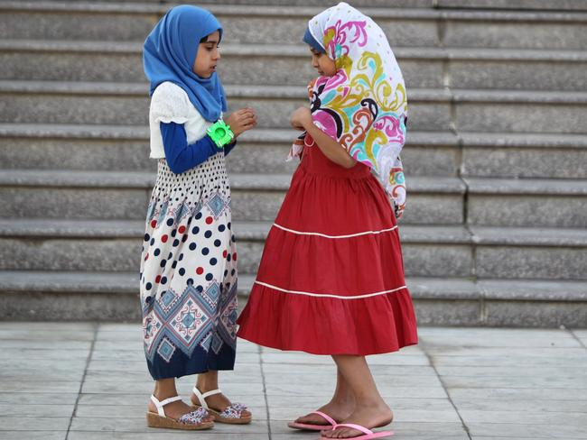 New moon ... Iraqi girls play outside a mosque in the capital Baghdad after attending prayers during the first day of Eid al-Fitr, which marks the end of the fasting month of Ramadan.