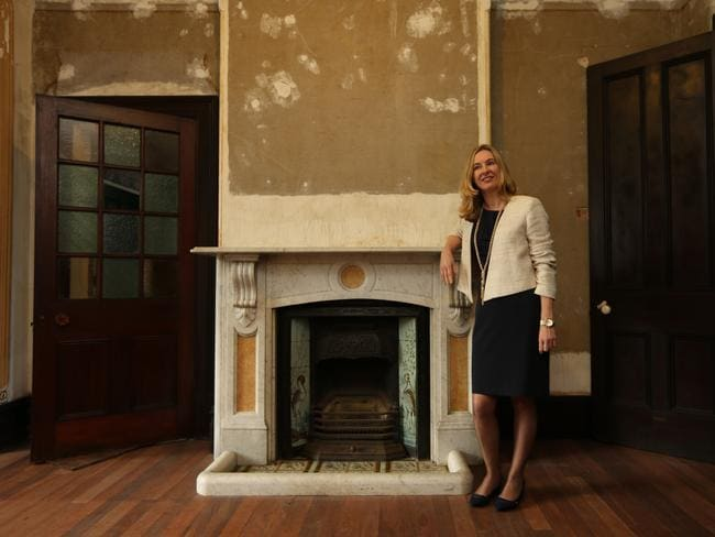 Real Estate Agent Louise Snowden beside one of the period fireplaces with detailed picture tiles. Picture: Tim Hunter