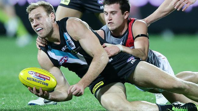 Jack Hombsch gets a handball away as he is tackled by Jackson Merrett. Picture: Sarah Reed.