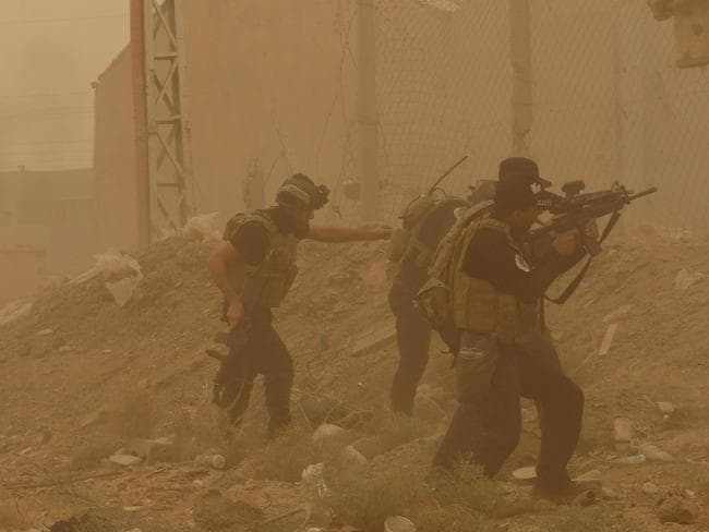 Attack ... security forces defend their headquarters against attacks by Islamic State extremists during a sand storm in the eastern part of Ramadi, the capital of Anbar province, on May 14. Picture: AP