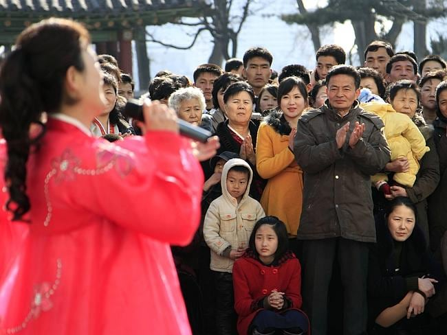Singing Kim's praises ... people gather to watch a performer sing near an election site in the Central District near Taedong Gate, in Pyongyang.