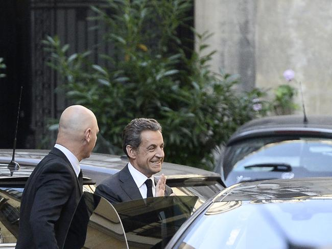 Still smiling ... Nicolas Sarkozy (right) gets into a car outside his offices in central Paris after an interview with French radio network Europe 1 and French TV channel TF1.