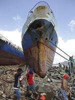 Survivors walk by a large ship after it was washed ashore by strong waves caused by powerful Typhoon Haiyan in Tacloban city, Leyte province, central Philippines. (Aaron Favila)