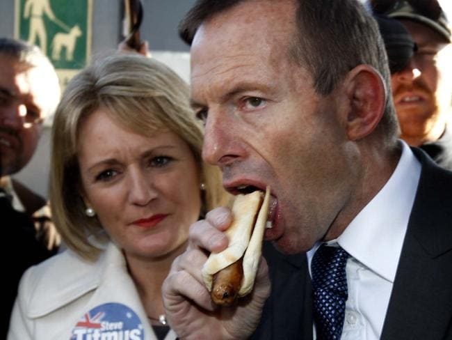 Meat eater ... Former PM Tony Abbott devours a sausage sandwich while campaigning at Launceston, Tasmania. Picture: Supplied
