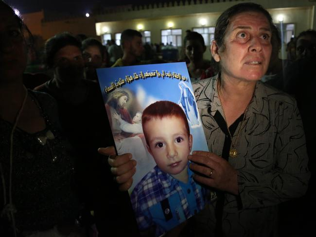 A displaced Iraqi Christian woman holds a picture of her four-year-old relative, David, who was killed by militants. PiIcture: AP/Khalid Mohammed