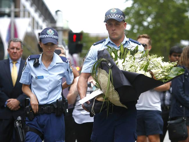 Police officers visit the flower memorial in Martin Place after the siege ended overnight. Picture: Bradley Hunter