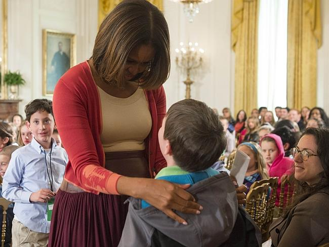 Greeting children ... US First Lady Michelle Obama talks to one of the children after answering questions from Executive Office employees at the White House. Picture: Saul Loeb