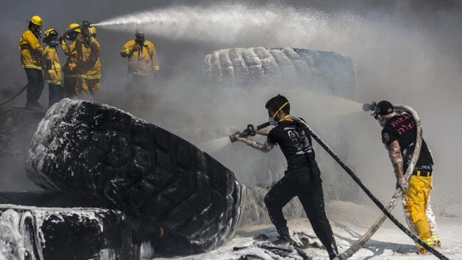 Israeli firefighters extinguish tractor tyres in a farmland set on fire by a kite with attached burning cloth launched from Gaza on the Israeli side of the border. Picture: AP