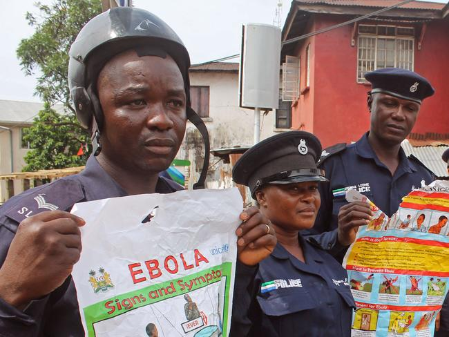 Warnings ... Sierra Leone police officers hold up posters as they try to educate people about the deadly Ebola virus in the city of Freetown, Sierra Leone. Picture: AP