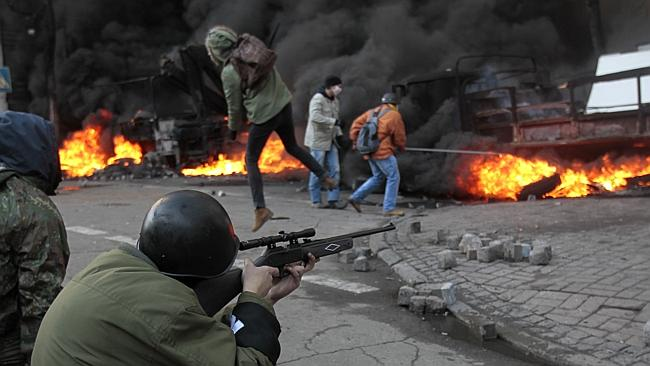 An anti-government protester shoots during clashes with riot police outside Ukraine's parliament in Kiev.