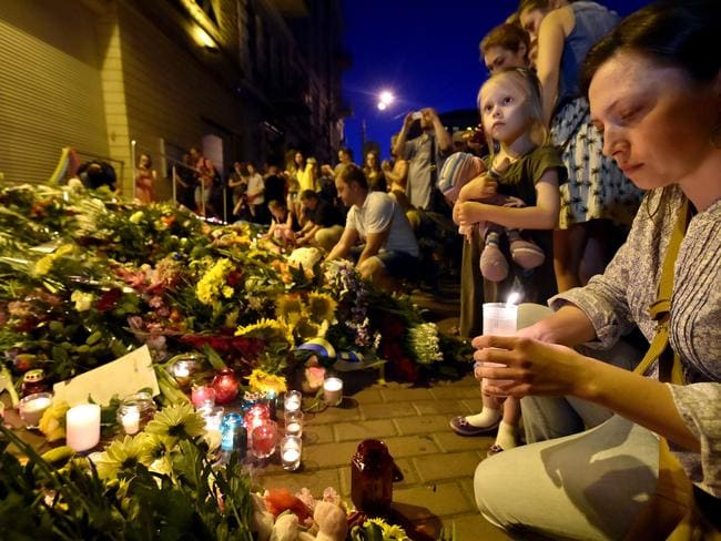 A woman lights a candle in front of the Embassy of the Netherlands in Kiev, to commemorate passengers of Malaysian Airlines flight MH17. Picture: AFP
