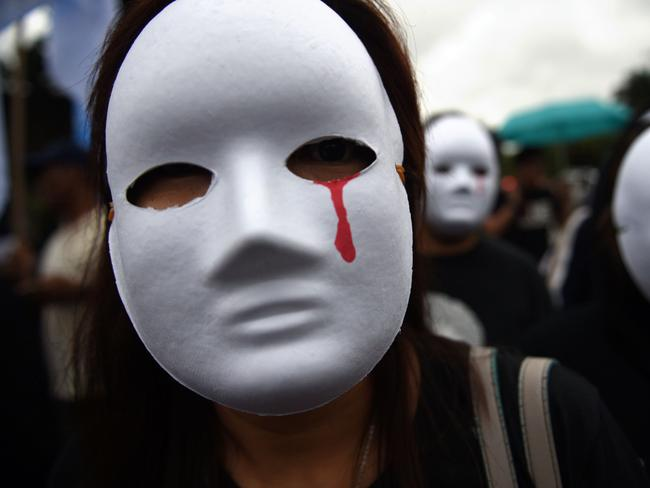 Protesters wear masks depicting victims of extra judicial killings. Picture: Ted Aljibe