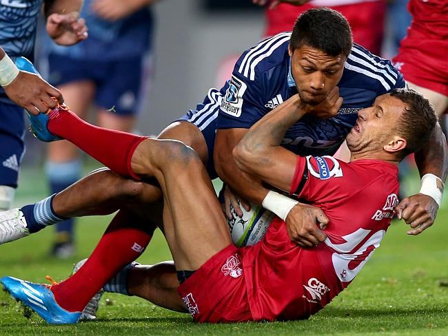Quade Cooper of the Reds is crunched by George Moala in the Reds' heavy loss to the Blues.