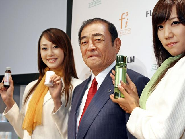 Japan's camera giant Fujifilm CEO Shigetaka Komori (C) showing off the company's new three skin care items (R green bottles) and dietary supplements (L) in Tokyo. Picture: Yoshikazu Tsuno