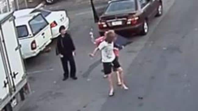 The man in the pink shirt charges at the victim with the hammer, hitting him in the head. Picture: Queensland Police