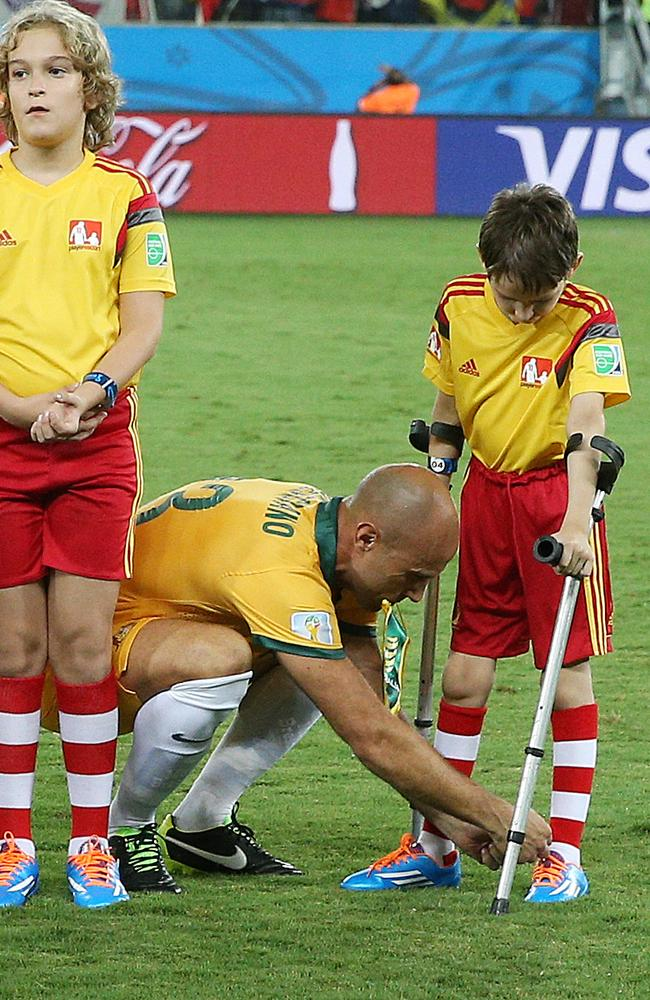 Australia's Mark Bresciano comes out with a boy on crutches and help him tie up his shoe laces. Pic: George Salpigtidis.