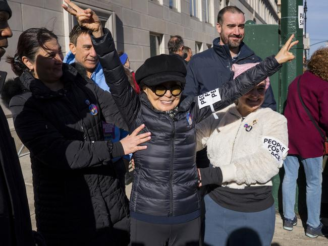 Yoko Ono shows the peace sign as she waves to people taking part in a march highlighting equal rights and equality for women in New York. Picture: AP