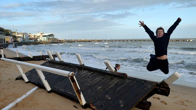 Rafe jumps for joy after the pier washed up on the beach. Picture: Nicole Garmston