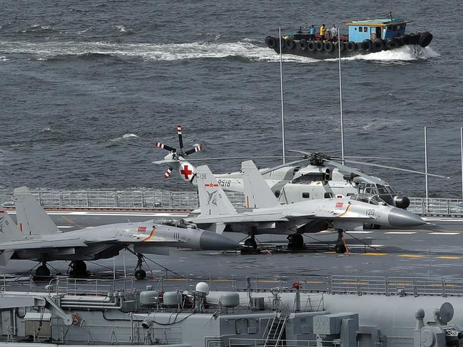 Fighter jets and a helicopter sit on the deck of China's first aircraft carrier the Liaoning. Picture: AP