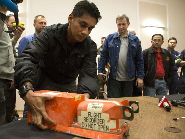 The handover ... a Malaysian investigator receives a black box from Malaysia Airlines Flight 17 from people who claimed to be officials from the Donetsk People's Republic. Picture: Dmitry Lovetsky