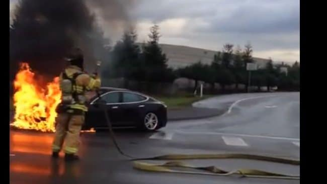 A firefighter tries to put out a fire in this Tesla.