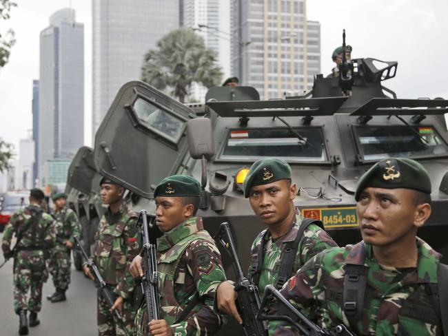 Indonesian soldiers stand guard ... near the site where an explosion went off in Jakarta with army tanks. Picture: AP