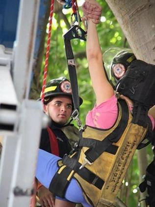 Guided down from up high ... The 23-year-old lovebird holds on for grim death as she is about to be brought down. Picture: Miami Fire Rescue