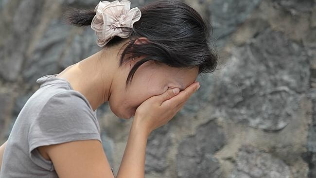 A woman mourns at the spot where Eunji Ban's body was found . Picture: Tim Marsden