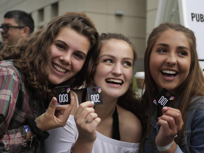 Teenage fans show off the their tokens for admittance to the civil case involving Taylor Swift. Picture: Joe Mahoney/Getty Images