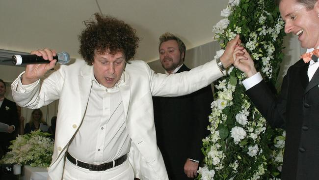 Leo Sayer holds the hand of Jason Kerr as he performs at the wedding.