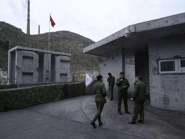 Tour guides hang outside waiting to take tourists inside the bunker. Picture: AFP/Wang Zhao
