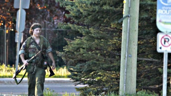 This heavily armed man was identified by police as Justin Bourque. He walks through Moncton, New Brunswick after several shots were fired in the area. He was spotted three times Thursday but has so far eluded a massive manhunt. Picture: AP Photo/The Canadian Press
