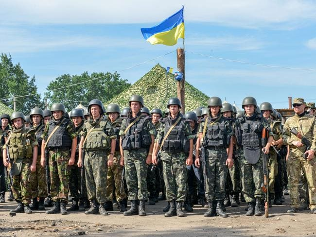 Ukrainian servicemen stay on line during a minute of silence commemorating their dead friends.