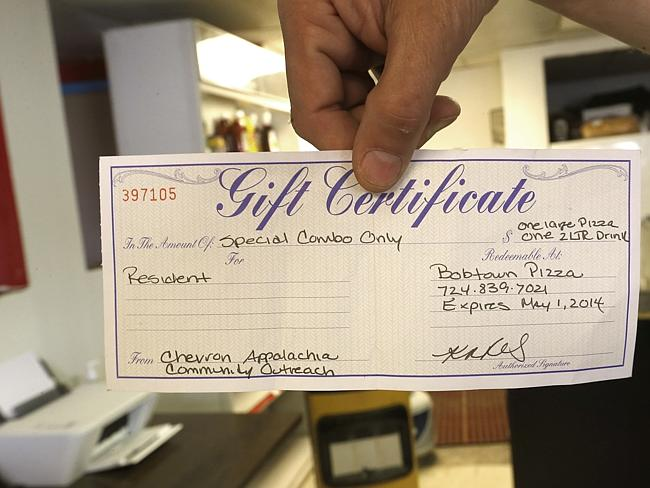 Free pizza ... Bobtown Pizza's Bill Sowden, shows a certificate that was redeemed at his shop in Bobtown.
