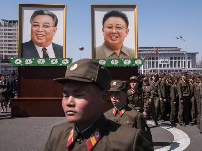 Korean People's Army (KPA) soldiers walk before the portraits of late North Korean leaders Kim Il-Sung (L) and Kim Jong-il (R) following the opening ceremony for the Ryomyong Street housing development in Pyongyang. Picture: AFP