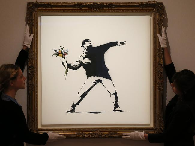 A spray paint work by Banksy is adjusted at Bonhams auction house in London.