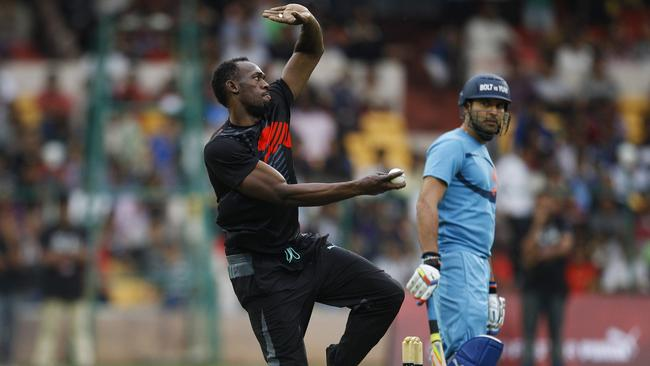 Indian cricketer Yuvraj Singh, right, watches Jamaican sprinter Usain Bolt bowl during the promotional match.