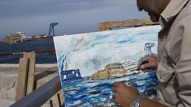 Artist Nino Taravella works at a painting of the Costa Concordia. (AP Photo/Andrew Medichini)